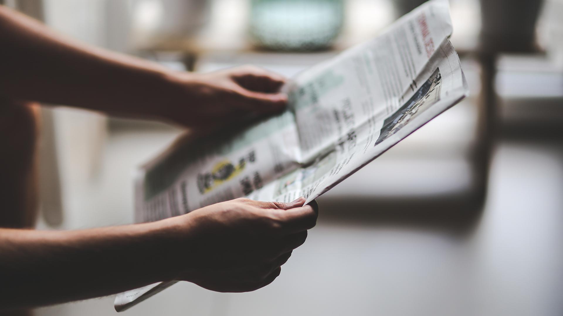 Person som håller i i en tidning.