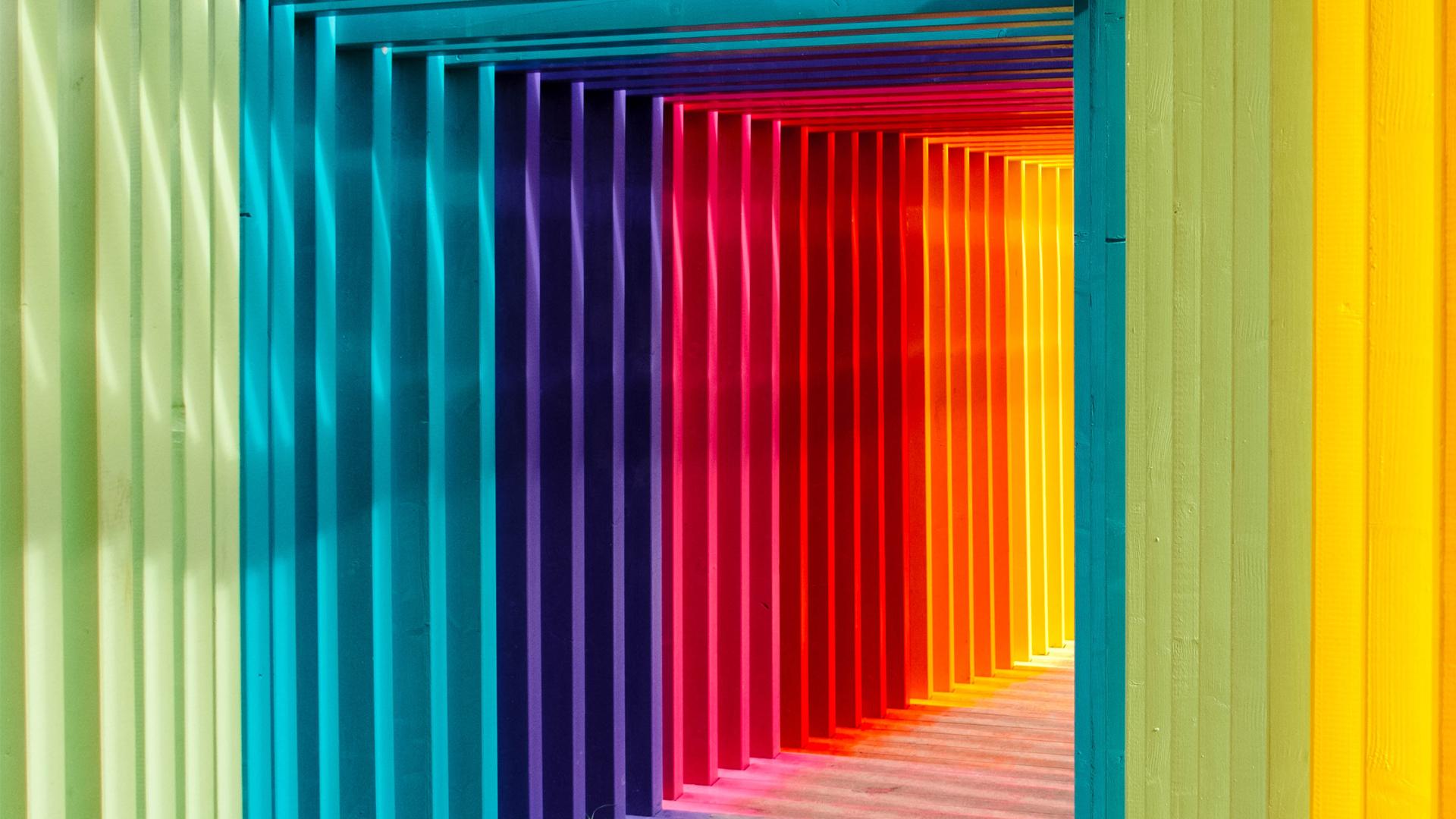 Korridor med en regnbåge av färger på väggarna.